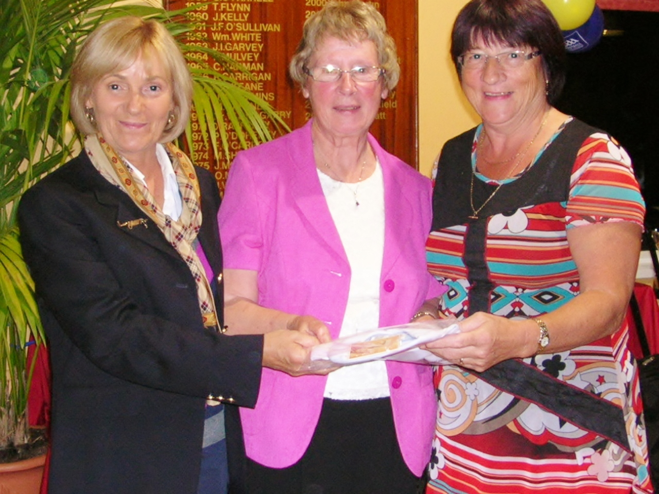Brigid Mannion is presented with Second Prize in Sam Beag By Lady Captain Mary King and Teresa Kenoy