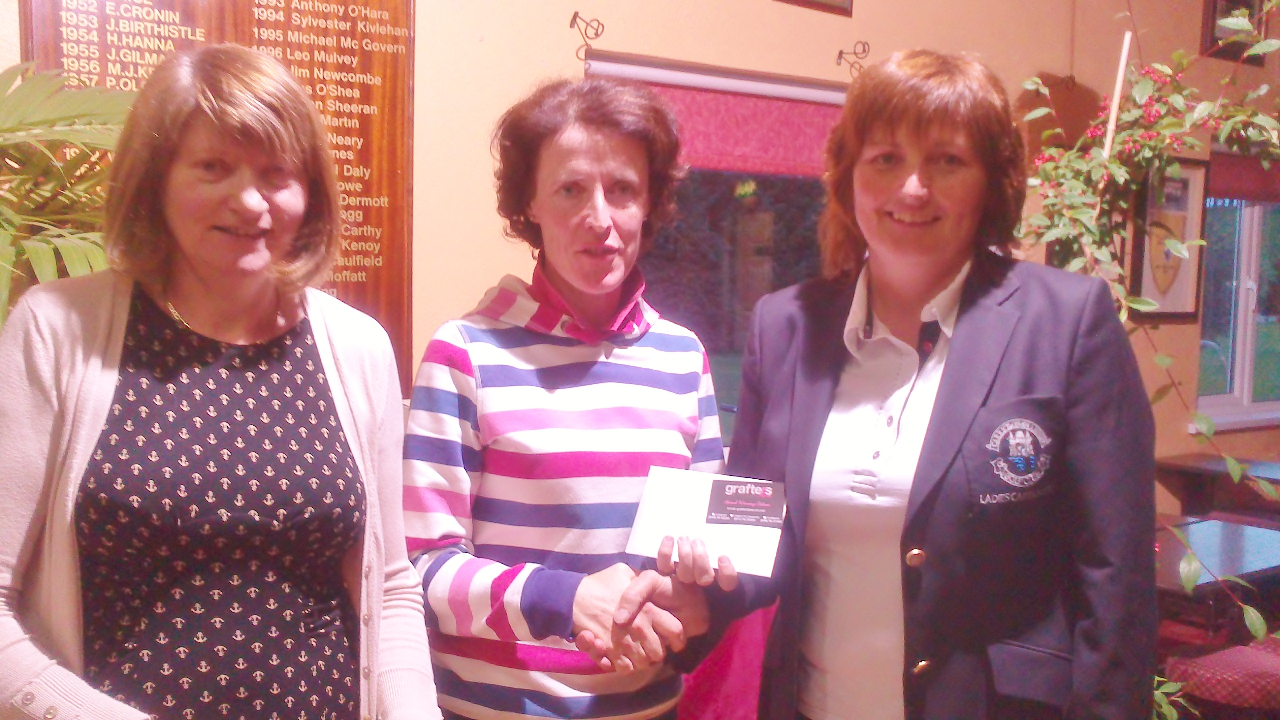 Ger Farry is presented with Gross Prize in  Grafters Hair Salon Stableford by Lady Captain Dolores Mulvey and Vice Captain Mary Molloy.