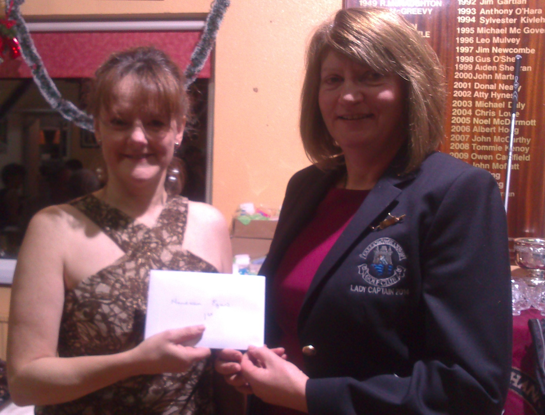 Elizabeth Muldowney accepts First Prize in Supervalu Turkey on behalf of Maureen Egan from Lady Captain  Mary Molloy.